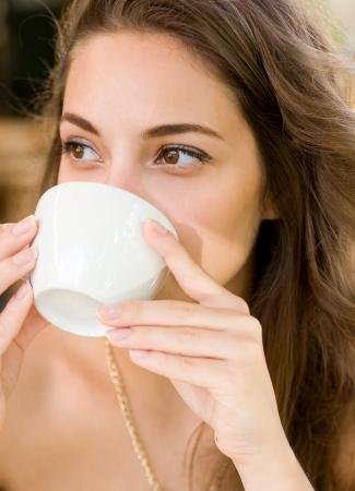 tomando café: Retrato de una belleza morena disfrutando de su café.