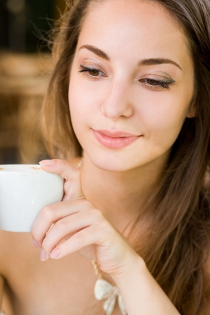 Closeup portrait of a gorgeous brunette in the coffee shop.