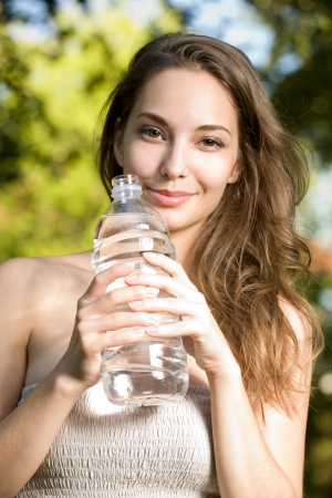 sediento: Retrato de una hermosa mujer joven morena disfruta de agua limpia y fría. Foto de archivo