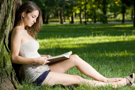 sitting down: Immersed in reading, young brunette woman outdoors with book.
