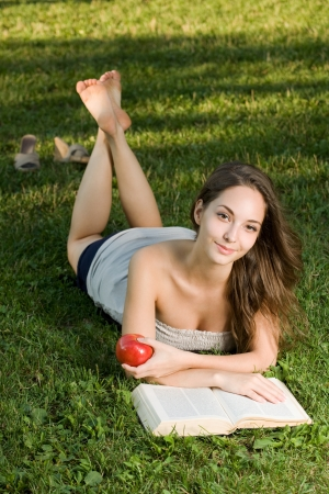 Portrait of a brunette beauty enjoying book outdoors in the park. photo