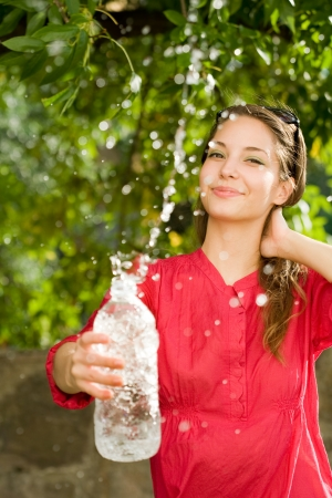 Precious sweet water, portrait of a beautiful young brunette woman with bottled water. photo