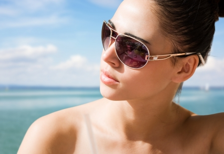 sunglasses beach: Sunny portrait of a young brunette relaxing at the beach. Stock Photo