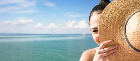 straw hat: Sunny portrait of a young brunette relaxing at the beach. Stock Photo