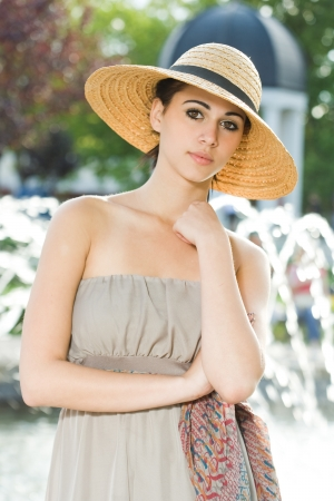 Outdoors fashion portrait of a beautiful young brunette in gray summer dress.