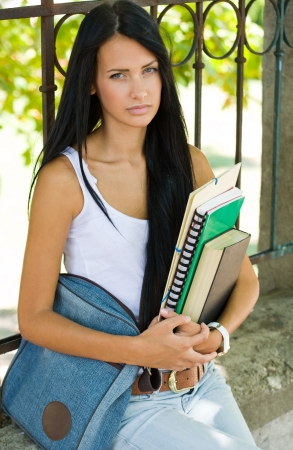 school bags: Portrait of a very tanned gorgeous young brunette student girl outdoors holding exercise books.