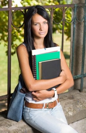 school girl sexy: Portrait of a tanned student beauty outdoors in the park with her exercise books. Stock Photo