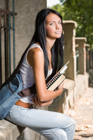 sexy school girl: Portrait of a tanned student beauty outdoors in the park with her exercise books. Stock Photo