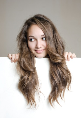 Portrait of a cute young brunette teen with white banner, showing off long hair. photo