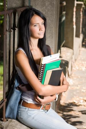 skinny jeans: Retrato de una atractiva estudiante morena joven al aire libre con los libros de ejercicios.