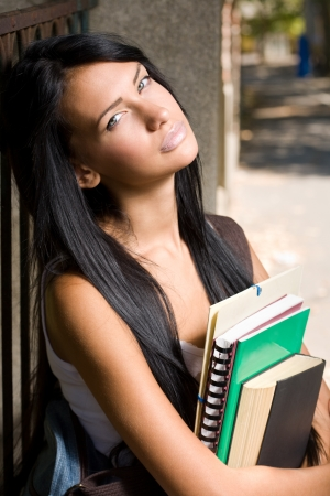 school girl sexy: Portrait of an attractive young brunette student outdoors with exercise books.
