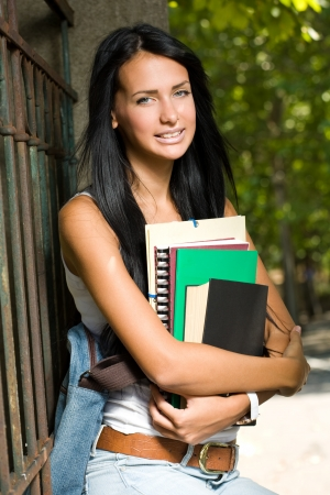 Portrait of an attractive young brunette student outdoors with exercise books. photo