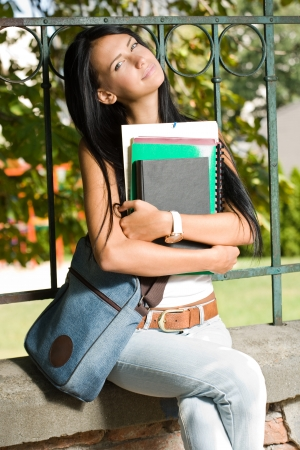 Outdoors portrait of a gorgeous young brunette student. photo