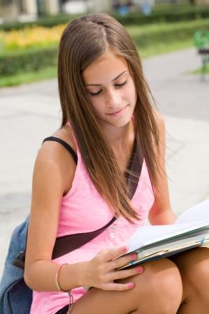 pantalones abajo: Retrato de una joven estudiante muy joven linda al aire libre, con sus libros de ejercicios.