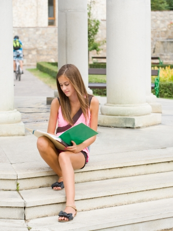 Portrait of a very cute young student girl outdoors with her exercise books. photo