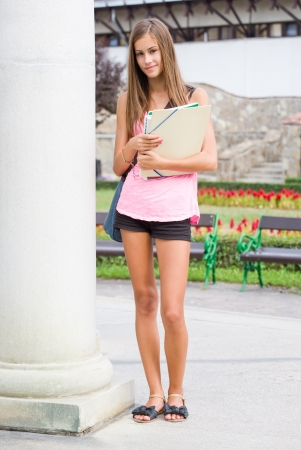 Portrait of a gorgeous young brunette student girl in the park. photo