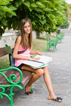 Portrait of a beautiful young student girl studying outdoors. photo