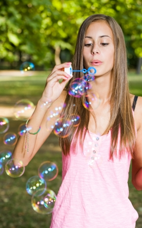 Portrait of a beautiful tanned young girl blowing colorful soap bubbles. photo