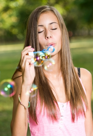 Gorgeous young teen girl blowin colorful soap bubbles outdoors. photo