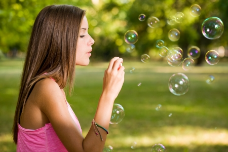 Free the bubbles, portrait of a beautiful young girl having fun outdoors blowing soap bubbles. Stock Photo - 15005475