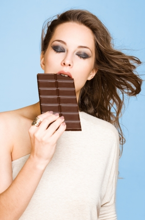 Portrait of a young brunette chocolate loving beauty on vibrant blue background. photo