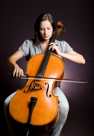 immersed: Portrait of beautiful young cellist immersed passionate in her music.