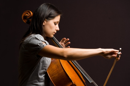 Portrait of beautiful young cellist immersed passionate in her music. photo