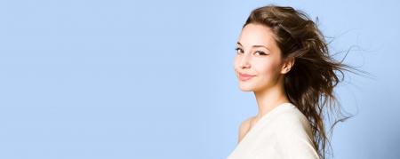 beauty shot: Beauty shot of a young brunette beauty on wide blue banner.