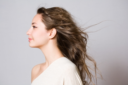 grey hair female: Profile portrait of a brunette beauty with windswept hair