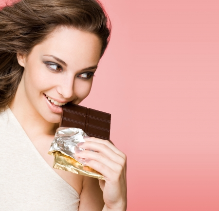 sideways glance: Portrait of a chocolate loving brunette beauty on pink background  Stock Photo