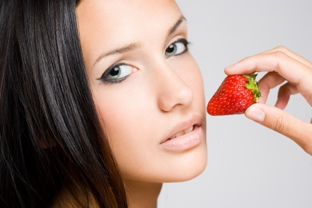 Glamorous portrait of a young brunette with strawberry. photo