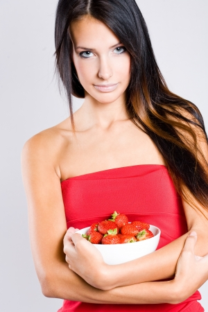 Portrait of a beautiful thin brunette with bowl of fresh strawberries. photo