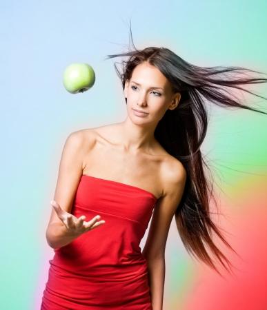 levitating: Vibrant healh girl with levitating apple on rainbow background. Stock Photo