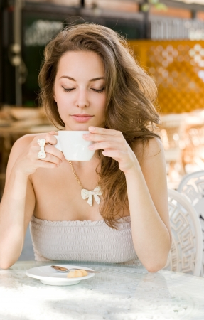 women holding cup: Portrait of a romantic looking hot coffee brunette lady. Stock Photo