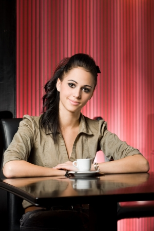 Portrait of a beautiful young brunette having her coffee. photo