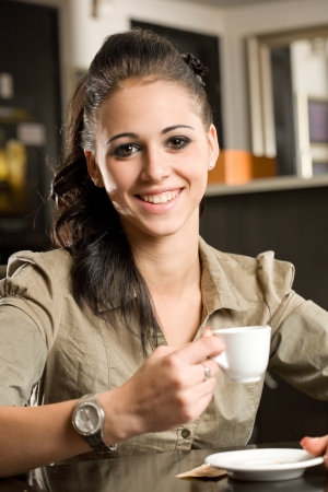 young woman sitting: Portrait of a beautiful fashionable young brunette woman having coffee.