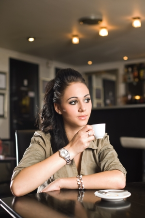 Portrait of a beautiful fashionable young brunette woman having coffee. photo
