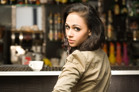 looking over shoulder: Portrait of a beautiful fashionable young brunette woman having coffee.