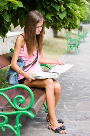 sitting down: Outdoors portrait of a beautiful tanned teen student girl.