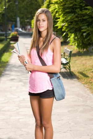 Outdoors portrait of a beautiful tanned teen student girl. photo