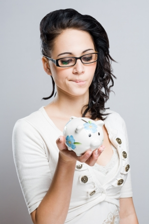 gone: Your savings are gone, worried young brunette holding piggy bank.
