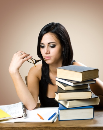 Portrait of a beautiful young brunette student with a large pile of books. Stock Photo - 15718839