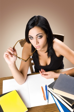 Portrait of a beautiful young brunette student with a large pile of books. Stock Photo - 15718852