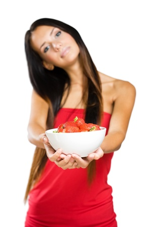 Half length portrait of a slender young brunette holdng bowl of strawberries. photo