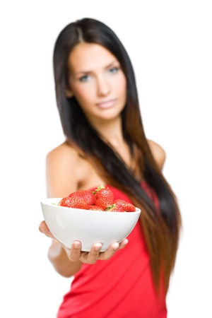 Portrait of a young beauty offering bowl of fresh strawberries. photo