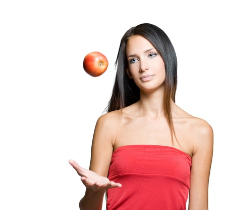 levitating: Portrait of a beautiful young brunette juggling fresh apple. Stock Photo