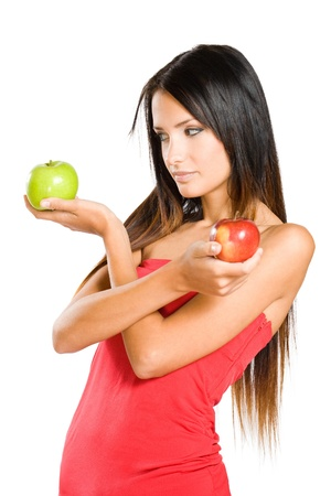 prefer: I prefer green, beautiful young brunette woman choosing between two apples. Stock Photo