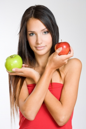 Half length portrait of a cute young brunette woman holding two apples. photo