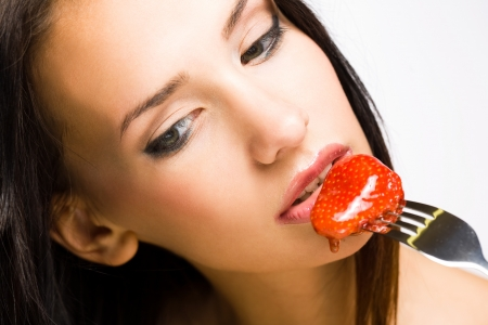 sexy food: Sensual strawberry, beautiful young brunette with honey covered strawberry.