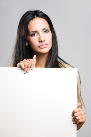 Portrait of a beautiful brunette woman holding a blank white sheet. Stock Photo - 15785426